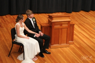 The couple sits on the stage watching the ceremony