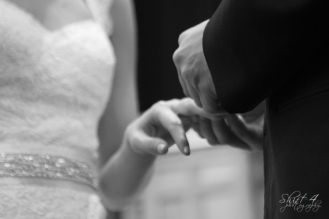 Joel slides the ring on to his bride's finger.