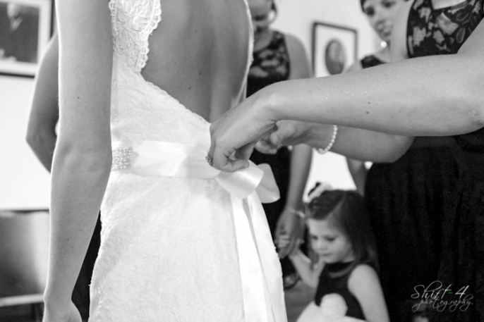 Liza's mother prepare the final touches on Liza's dress while her younger neice looks on in the background