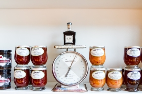A jar of of Blaak Drizzle sits on the shelf amongst the collection of knickknacks that line the walls